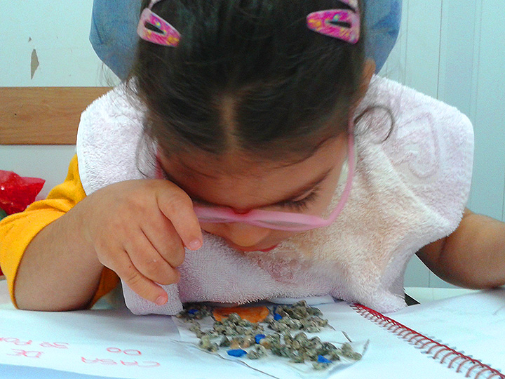 A deafblind child stares at a notebook.
