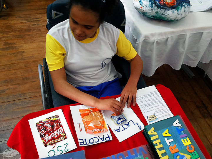 Photo from Ahimsa - A girl stares at paper drawings on a table