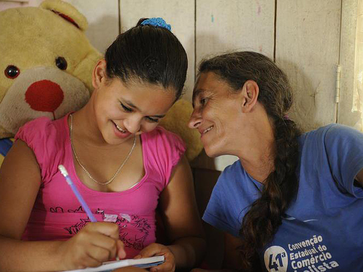 Photo from Projeto Resgate - A child writes on a notebook while an adult woman stares happily at her