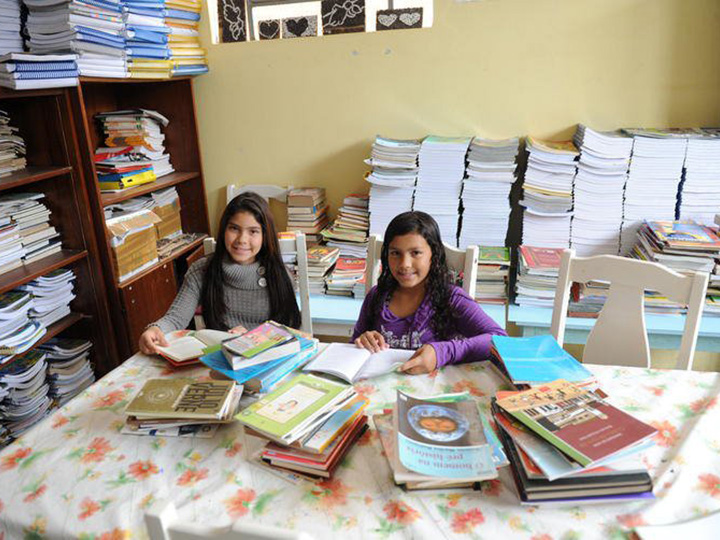 Photo from Projeto Resgate - Two girls smile while exploring books at a library.