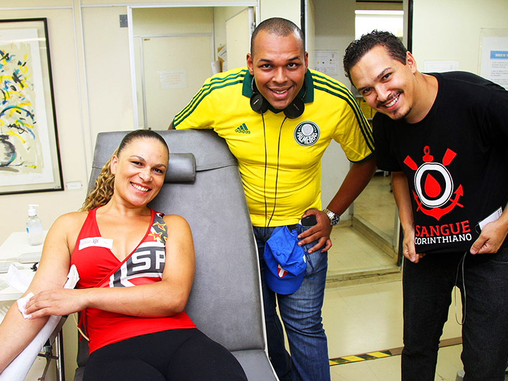 Photo from SobreVivência - Two men and one woman wearing different soccer team jerseys smile as the woman makes a blood donation