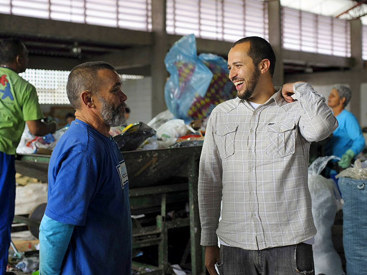 Two men talk in a recycling center background